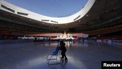 Дети катаются на коньках на Олимпийском стадионе в Пекине.