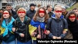 Учасники віча «Зупинимо капітуляцію!» із «червоною лінією» на обличчях під час час здійснення обходу урядового кварталу. Київ, 6 жовтня 2019 року