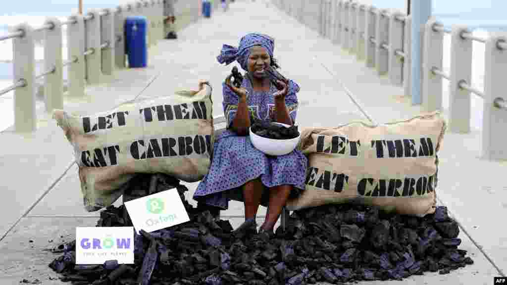 An activist from the British charity Oxfam stages a protest during UN climate change talks in Durban, South Africa, on December 9. (Photo for AFP by Stephane De Sakutin)