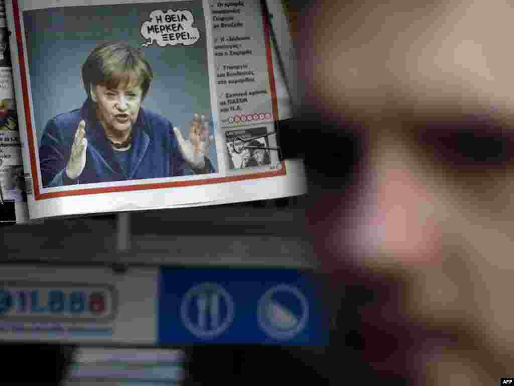 "A photograph of German Chancellor Angela Merkel with the caption ""Auntie Merkel Knows..."" is seen on the front page of the ""Pontiki"" newspaper at a newstand in central Athens. (Photo for AFP by Angelos Tzortzinis)"