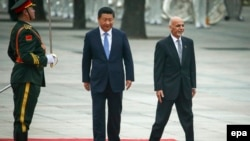 Afghan President Ashraf Ghani (right) and Chinese President Xi Jinping (center) review a guard of honor during a welcoming ceremony outside the Great Hall of the People in Beijing, China, on October 28.