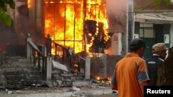 Men walk past a burning building during the 2010 violence in the Kyrgyz city of Osh that left hundreds dead.