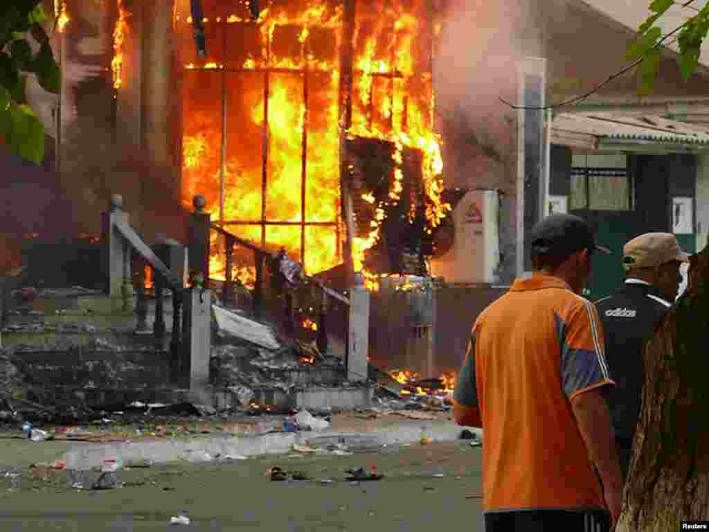 Men walk past a burning building in Osh on June 11, when at least 12 people died in the unrest.