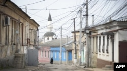A woman walks along a street of the old town of Simferopol.
