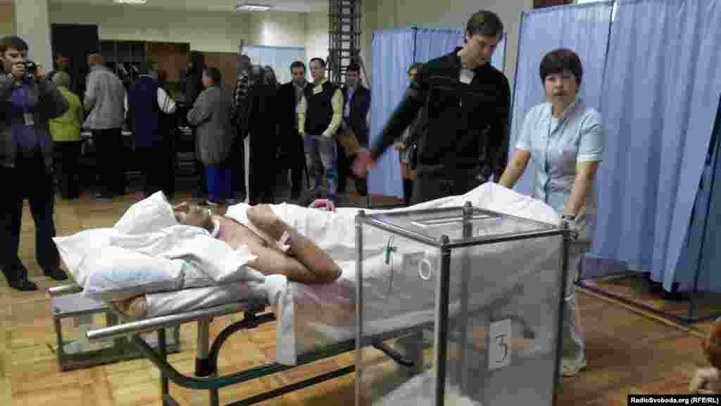 Лежачий хворий голосує на виборчій дільниці у Харкові