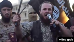 Ethnic Albanian Kosovar Lavdrim Muhaxheri (holding microphone) appears in an IS video calling on Albanian Muslims to join militants fighting against Syrian President Bashar al-Assad.