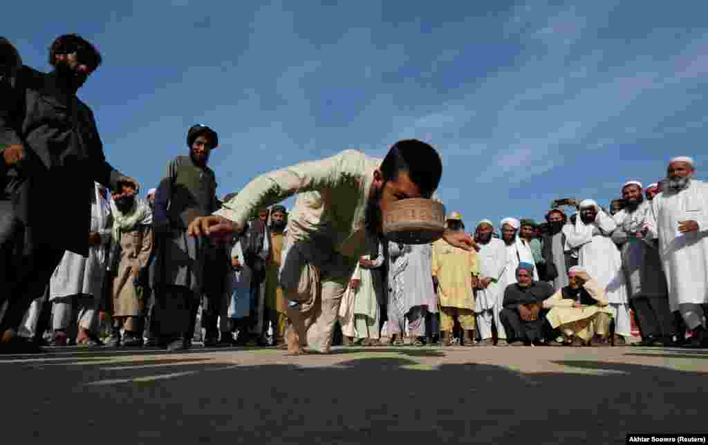 "In Islamabad, Pakistan, a supporter of the religious and political party Jamiat Ulema-e-Islam plays the traditional game of ""topai"" (cap) during an opposition march to protest the government. (Reuters/Akhtar Soomro)"