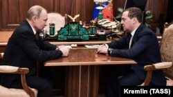 Russian President Vladimir Putin (left) meets with Dmitry Medvedev at the Kremlin in Moscow on January 15.