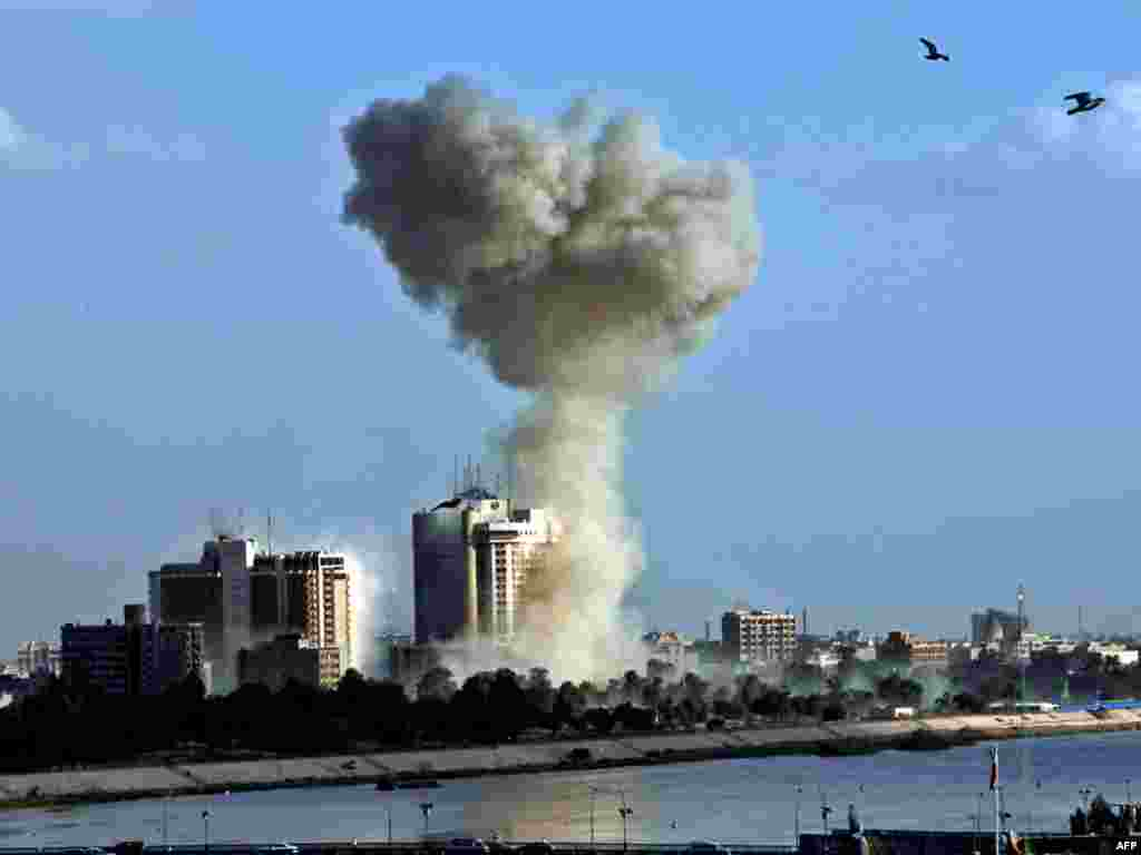 Smoke rises from an explosion near the Palestine Hotel in Baghdad on January 25. - Three bomb blasts struck central Baghdad in close succession, ending a six-week lull in coordinated attacks in the capital. Photo by AFP