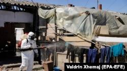 Një punëtor komunal, dezinfekton kampin ku jetojnë romët në Plementin. Prill, 2020.