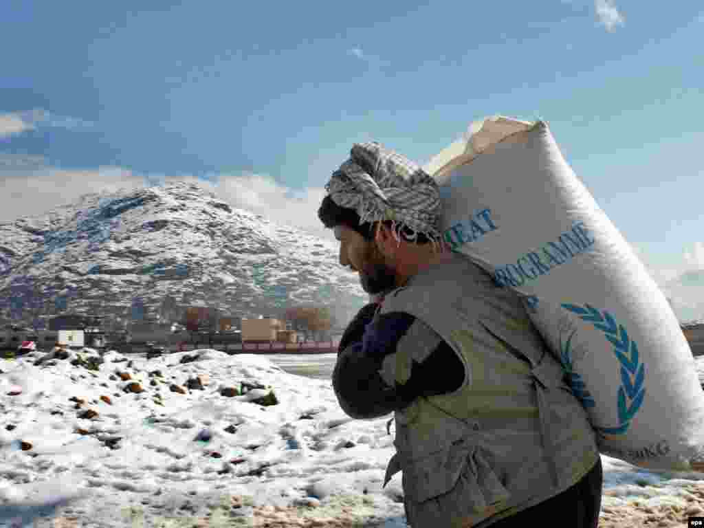 A man carries flour distributed by the World Food Program on a snow-covered path in Kabul.