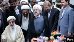 Iranian President Hassan Rouhani (C) and Ayatollah Ahmad Jannati (L), the head of the Iran's Guardian's Council, undated.