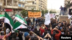 Antigovernment protesters in Syria wave flags and carry coffins during the funeral for two protesters killed in clashes in Homs on January 31.