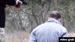 """Скриншот размещенного в Сети видео, в котором двое мужчин перед предполагаемой казнью """"признаются"""", что являются """"шпионами ФСБ""""."""