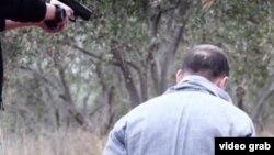Ребенок-боевик показан как исполнитель казни двух мужчин, которых называют «российскими агентами». Кадр видеозаписи.