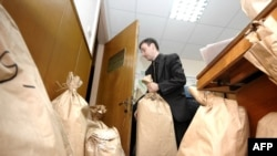 An election official handles bags of ballots while beginning the parliamentary vote recount at a polling station in Chisinau on April 15.