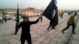 مسلح من تنظيم (داعش) يحمل علماً في الموصل