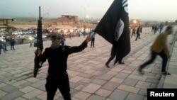 مسلح يرفع علم تنظيم (داعش) في الموصل