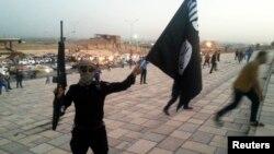 «Ислам мемлекеті» экстремистік тобы туын ұстаған қарулы адам. Мосул, 23 маусым 2014 жыл. (Көрнекі сурет.)