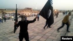 «Ирак пен Шам ислам мемлекеті» (ИЛИМ) ұйымының туын ұстап тұрған қарулы адам. Мосул, Ирак, 23 маусым 2014 жыл.