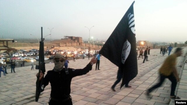 A fighter of the Islamic State of Iraq and the Levant (ISIL) waves an ISIL flag in the city of Mosul. The group has claimed wide swaths of territory in Iraq's north and west, including its second-largest city.