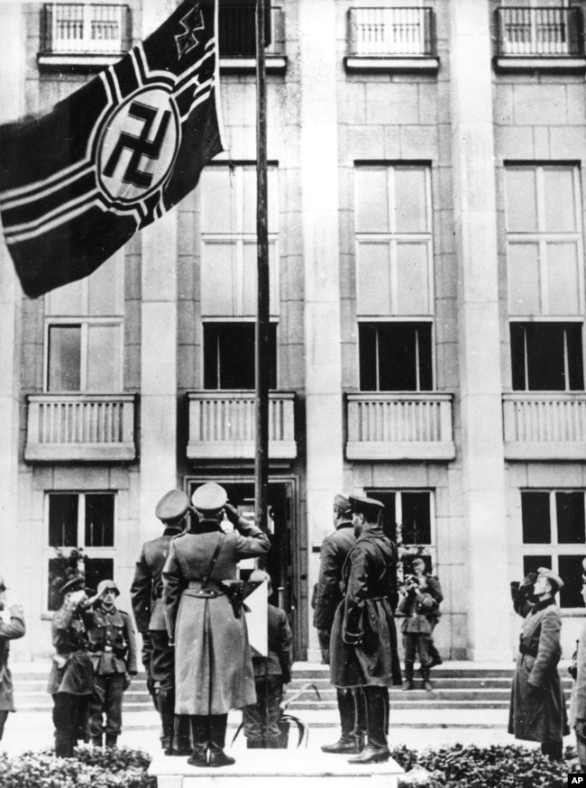Військовослужбовці нацистської Німеччини і СРСР віддають честь німецькому прапорові зі свастикою під час урочистостей у рамках військового параду з нагоди поділу земель, що належали до того Польщі. Брест-Литовський, 22 вересня 1939 року