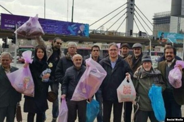 former Tehran University chancellor Mohammad Maleki and former hard-line columnist Mohammad Nurizad pose with colleagues during their trash-collecting protest on February 2.