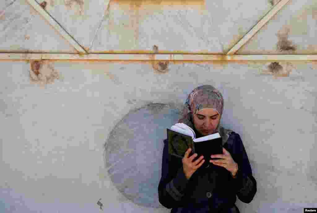 Палестинская женщина читает Коран в Иерусалиме. 10 июня 2016