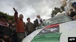 معترضان لیببایی در شهر درنه - بین طبرق و بنغازی در شرق لیبی- پرچم سابق این کشور را بر روی یک ماشین قرار داده اند.