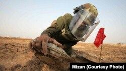 یک سرباز ایرانی در حال خنثی کردن یک مین برجا مانده از زمان جنگ ایران و عراق