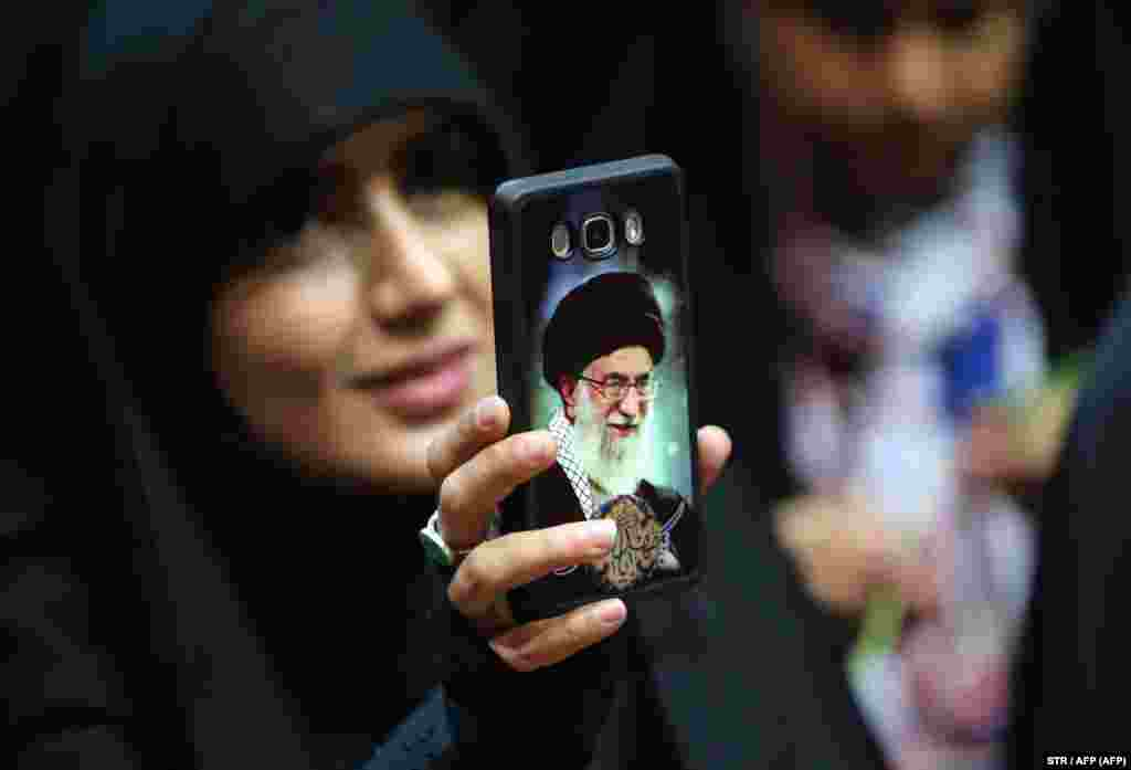 An Iranian woman shows her phone cover depicting Iran's Supreme Leader Ayatollah Ali Khamenei as she attends a rally to support head scarves in Tehran. (AFP)