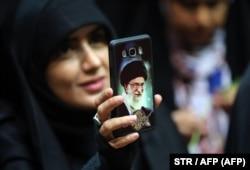 زن ایرانی با عکس رهبر معظم انقلاب ، آیت الله علی خامنه ای ، ماسکی را بر روی تلفن خود نشان می دهد.  بسیاری هشدار می دهند که سانسور اینترنتی مورد بحث می تواند فاصله بین ایرانیان و روحانیت را بیشتر کند.