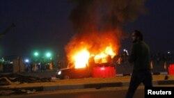 Каирдегі қақтығыс кезінде өртенген полицей көлігі маңында тұрған адам. 8 ақпан 2015 жыл.
