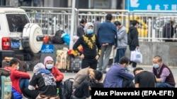 Маска таққан адамдар темір жол вокзалында. Гуанчжоу, Қытай.