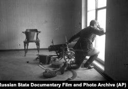 Пулеметчик обустраивает позицию в одном из жилых домов во время революционных боев в Москве, ноябрь 1917 года