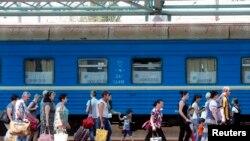 Пасажири йдуть вздовж платформи головного залізничного вокзалу у Донецьку, липень 2014 року