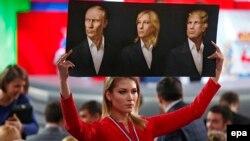 O jurnalistă, ținând un poster cu portretele lui Vladimir Putin, Marine Le Pen și Donald Trump, înaintea conferinței de presă anuale a liderului de la Krenlin