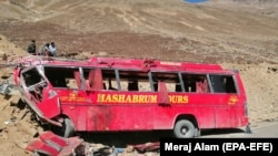 FILE: People stand beside the wreckage of a passenger bus at the scene of its accident near Chilas in Gilgit-Baltistan in September 2019.