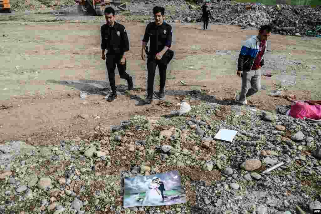 Turkish police officers walk past a wedding photograph in a dump in Diyarbakir in southeastern Turkey. Rubble from destroyed homes has been dumped at this site following months of clashes between Kurdish militants and Turkish government forces in Sur district. (AFP/Ilyas Akengin)