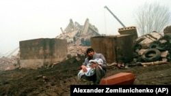 A man holds the body of his dead child in Gyumri. The quake lasted just 20 seconds, with a magnitude of 6.8, but the dust cleared to scenes of utter devastation.