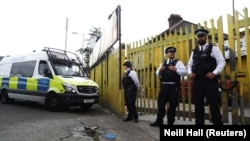 Police officers stand outside a property that was raided in Newham, East London, on June 5, as part of the investigation into the London attacks on June 3.