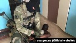 Працівник СБУ затримує підозрюваного в інтернет-шахрайстві