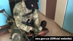 Работник СБУ задерживает подозреваемого в интернет-мошенничестве