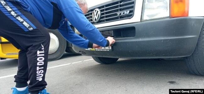Një shofer nga Serbia duke mbuluar targat e veturës së tij.