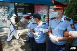 Оппозиция ұйымдастырған митинг кезінде полицейлер жетектесіп көшені жапты, жұмысшылар залалсыздандыру жұмысын жүргізді. Алматы, 6 маусым 2020.
