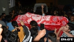 People carry the body of Babar Qadri during a funeral procession in Srinagar on September 24.