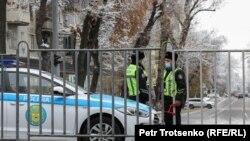 Сотрудники полиции у металлической ограды рядом с местом проведения одобренной властями акции в Алматы. Иллюстративное фото.