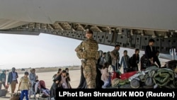Brit és kettős állampolgárok szállnak fel egy katonai gépre a kabuli repülőtéren 2021. augusztus 16-án