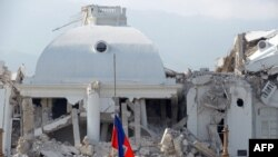 Haiti -- A Haitian national flag flies half mast at the collapsed presidential palace as a soldier patrols in Port-au-Prince, 20Jan2010