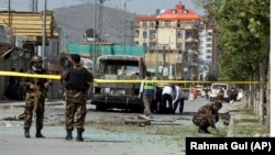 Security forces and medical workers attend the scene of a deadly bomb attack in Kabul in June.